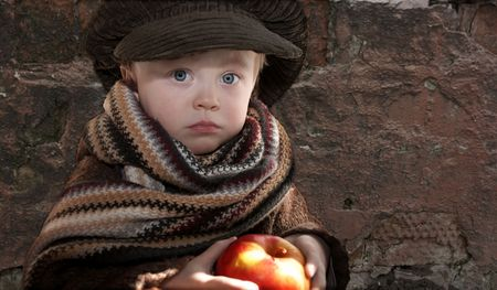 little sad child with red apple, copy space on grange wall background photo