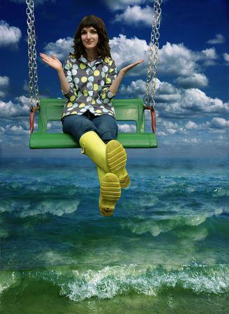 happy young brunette in yellow wellingtons swinging between sky and sea photo