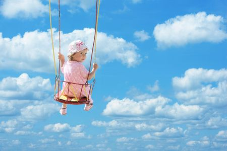 happy cute child swinging in blue summer sky