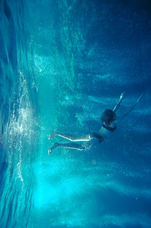 freediving girl with air bubbles and corals, and water surface Banco de Imagens