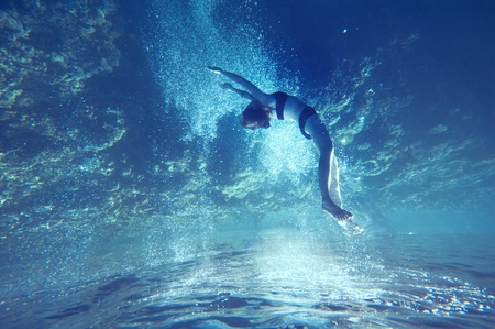 sunrays: freediving girl with air bubbles and corals, and water surface Stock Photo