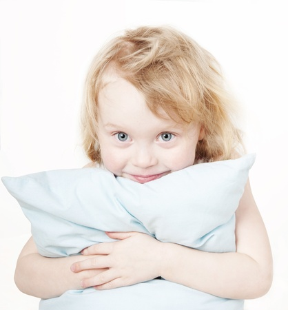 funny little girl hugs little blue pillow on white background