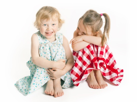 two 3 years old girls laughing in studio