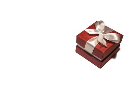 A beautiful red box with a white ribbon. Packaging for a gift on a holiday.
