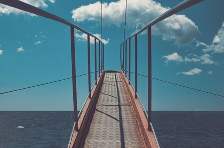 Bridge on the ship, leading up to jump into the open sea. Iron springboard with handrail upward