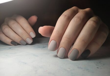 Gradient gray coating on short square nails. Matte finish on the manicure from light gray to dark gray.