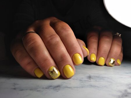 Clean manicure on thick fingers with yellow gel polish and gold sequin design