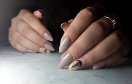 Perfect manicure with coffee gel polish. Long round nails with beige coating and ebony design