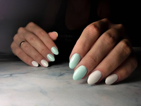 Long nails with pale blue coating and light beige design. Zdjęcie Seryjne