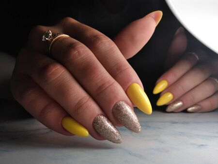 Yellow gel Polish with gold sequins. Long pointed nails with yellow coating and gold sprinkle design.