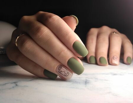 Long nails with manicure and coating. Gel lacquer matte green with camouflage design and painted face. Archivio Fotografico - 138552444