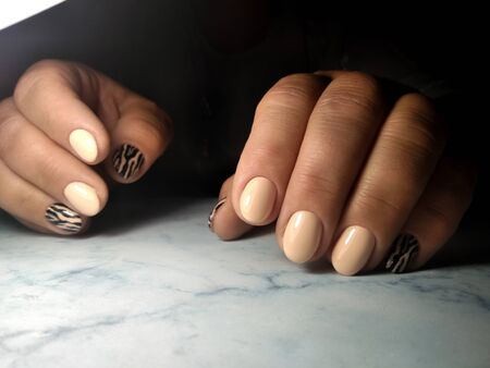 Camouflage gel Polish on short round nails. Beige coating with striped design. Tiger and leopard design.