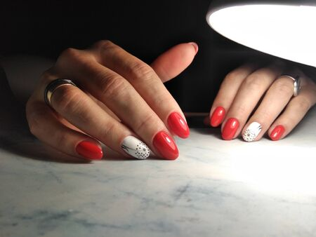 Beautiful manicure with red coating and white design. Long round nails with dandelion design on white background.