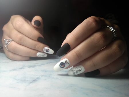 Clean and neat manicur with white and black coating design planet and owls Archivio Fotografico