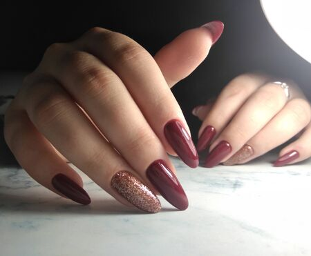 Long nails coated with red-wine color. Burgundy gel polish on long nails with sequins design