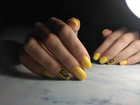 Yellow glossy gel Polish. Manicure with black owl design, painted on the ring finger