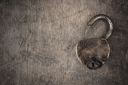 Old vintage lock with key. Ancient rusty barn lock with key on wooden textured background Banque d'images