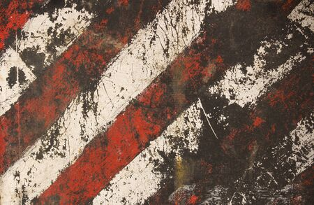 Striped damaged texture with cracks and white-red stripes.Post-apocalyptic background with colorful stripes. Destroyed sign dimensional transport with cracks and spots. Banco de Imagens
