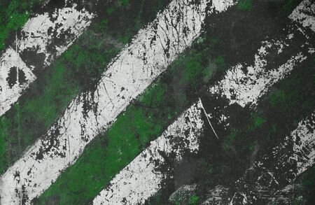 Damaged striped texture with cracks and the green and white stripes.Post-apocalyptic background with colorful stripes. Destroyed sign dimensional transport with cracks and spots.