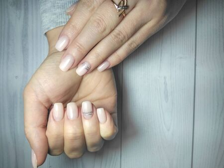 Womens manicure on long square nails. Gel lacquer camouflage color with design. A coating of beige color with silver stripes design. Zdjęcie Seryjne