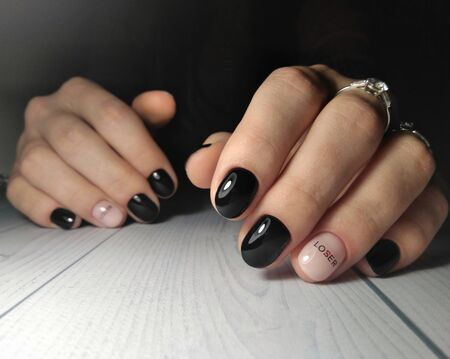 Womens hands with the gel polish. Glossy black finish with reflection and camouflage design. The inscription on the camouflage lover and loser