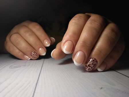 French manicure on womens thick handles with leopard design. Spotted black design on French gel varnishes Zdjęcie Seryjne
