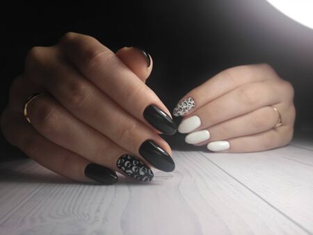 Black manicure with white leopard spots. White gel polish with a black leopard print design on a long round nails.