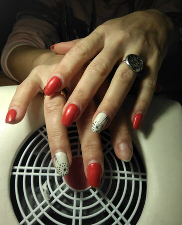 Women's pens with worn manicure on re-processing. Regrown gel polish without chips and fell off one nail. Women's hands on the nail vacuum cleaner.