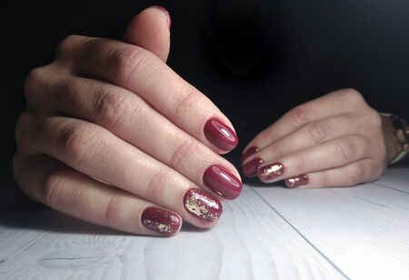 Short nails coated with red-wine color. Burgundy gel polish on long nails with sequins design