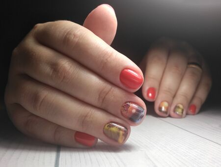 Short red nails covered with gel polish with design. Womens pens with manicure and red coating. Landscape yellow and orange sunset design Zdjęcie Seryjne