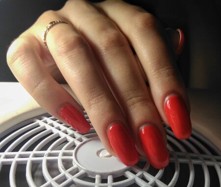 Women's pens with perfect worn manicure on re-processing. Regrown red gel polish without chips. Women's hands on the nail vacuum cleaner.