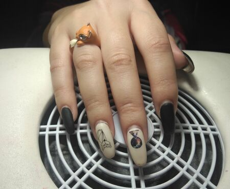 Women's pens with perfect worn manicure on re-processing. Regrown black and beige gel polish without chips. Women's hands on the nail vacuum cleaner. Foto de archivo