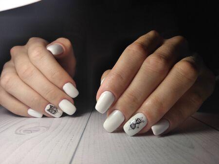 Weiße Nagelabdeckung mit schwarzem Wolfsdesign und Geometrie auf dunklem Hintergrund. Standard-Bild