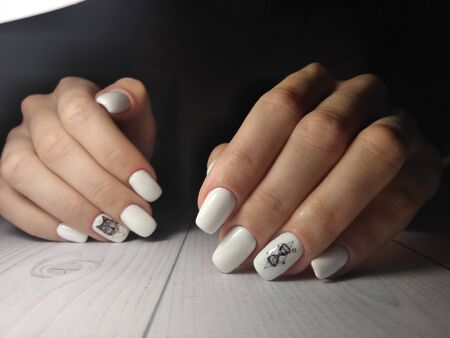 White nail cover with black wolf design and geometry on dark background. Imagens