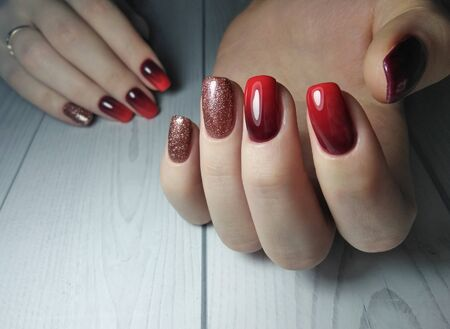 Long square nails covered with gel Polish with gradient design on wooden background. Red gradient on the nails. From black to red. Brilliant design.