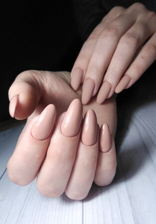 Long round nails with camouflage clean manicure. Beige gel polish with pastel color. Matte finish on one hand.
