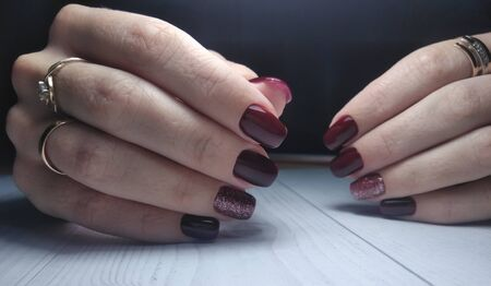 Long square nails with manicure. Gel polish with wine color and brilliant design. Maroon and red coating on the nails.