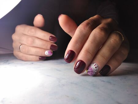 Stylish manicure with bard color and white flower design