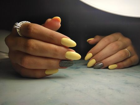 Yellow gel polish with grey design and sequins