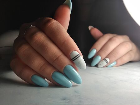 Blue gel lacquer with white design and black geometry on long nails