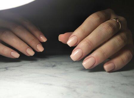 Gently pink manicure young girl on a dark background  Zdjęcie Seryjne