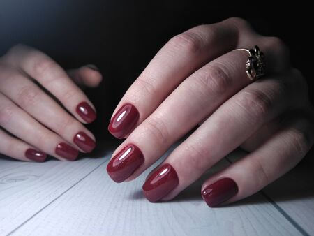 Red Burgundy lacquer on womens handles with sequin design. Beautiful manicure with the wine and Burgundy finish. Manicure work on a wooden table. Stockfoto