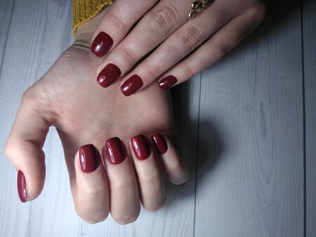 Red Burgundy lacquer on womens handles with sequin design. Beautiful manicure with the wine and Burgundy finish. Manicure work on a wooden table. Top view.