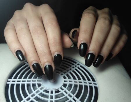 Women's pens with perfect worn manicure on re-processing. Regrown black gel polish without chips. Women's hands on the nail vacuum cleaner.