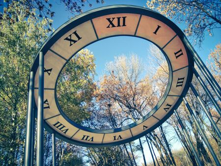 Large modern solar powered clock. The transition of time from one season to another. Electronic round clock in the city park with roman numerals. Concept of time. Banco de Imagens