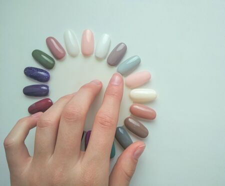 Tips for manicure in the form of chamomile. Palette of pastel colors. The customer chooses the color. Hand shows the color.