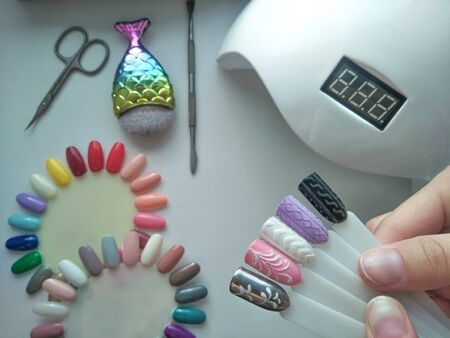 Pastel winter designs on the tips. Color palette. Stylish designs on nail tips similar to a knitted sweater on the background of manicure tools. UV lamp, brush and scissors on the master's desktop.
