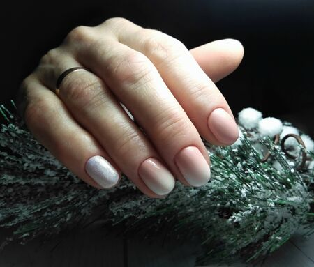 A neat manicure with a delicate design in pastel colors with a christmas tree branch covered with snow. Long square nails with gel polish and gradient design on the dark background.