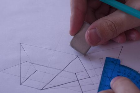 A man draws a diagram with a ruler, eraser and pencil. Design and create a project on a white sheet of paper close-up. Stockfoto
