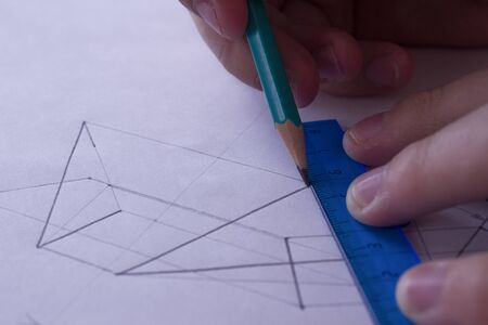 A man draws a scheme on white paper with a pencil using a ruler. Drawing project in pencil on a large sheet of close-up. Stockfoto